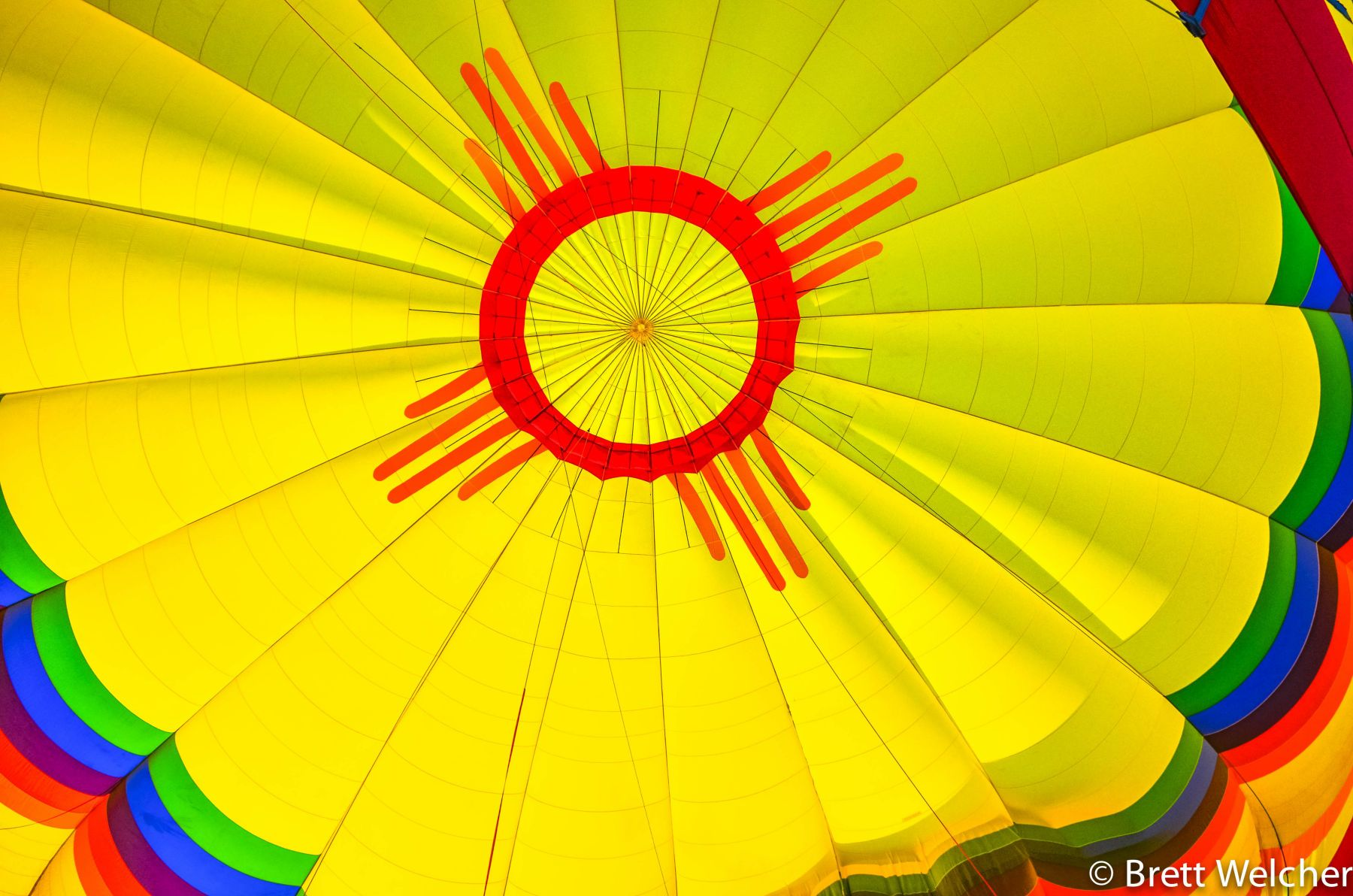 An image of the New Mexico state flag, reflected on top of a Rainbow Ryders hot air balloon. The colors of New Mexico's state flag are the red and yellow of old Spain. The simple, elegant center design is the ancient Zia sun symbol, which represents the un