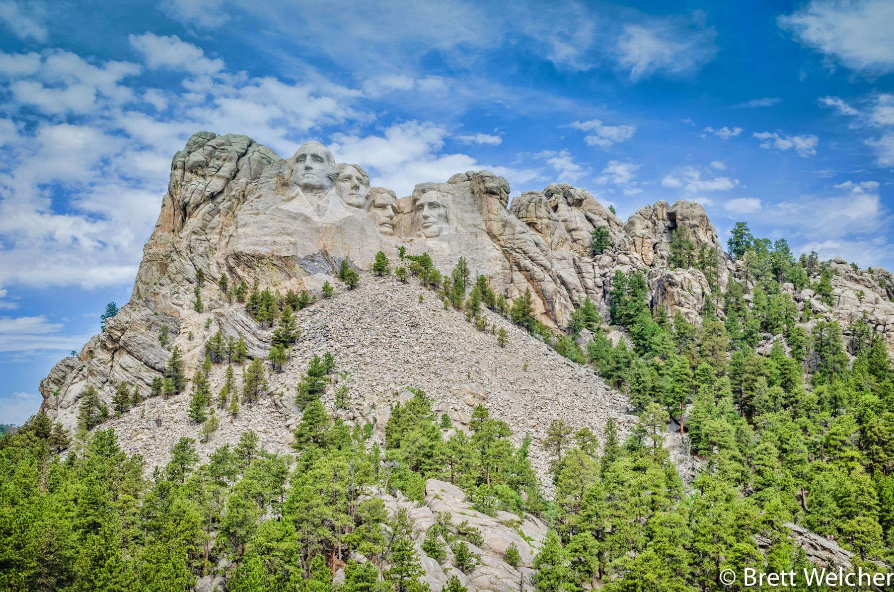 Mount Rushmore National Memorial is a sculpture carved into the granite face of Mount Rushmore near Keystone, South Dakota. Sculpted by Danish-American Gutzon Borglum and his son, Lincoln Borglum, Mount Rushmore features 60-foot sculptures of the heads of