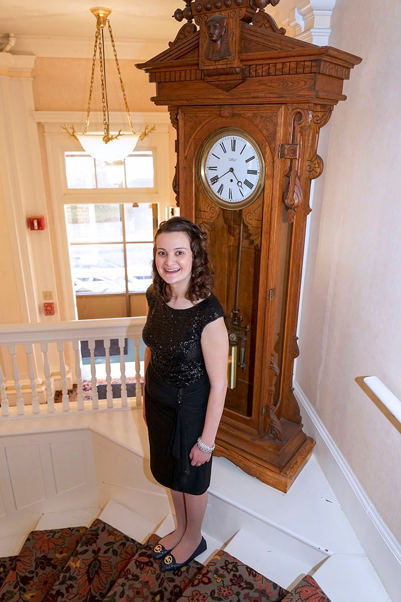 College Graduate Posing by a Grandfather Clock