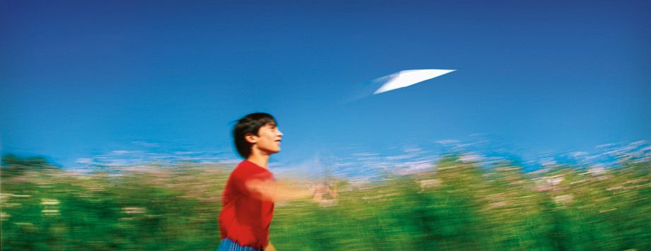 Boy flying a paper airplane.