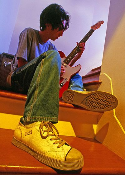 Teenage boy playing his Fender guitar with Fender shoes
