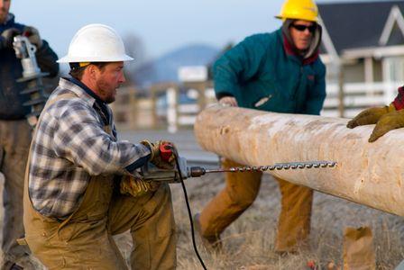 Linemen Drilling New Power Poles
