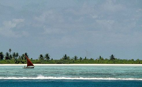 Red sailed boat runs the inside reef, Northern Maldives, Surfer Magazine