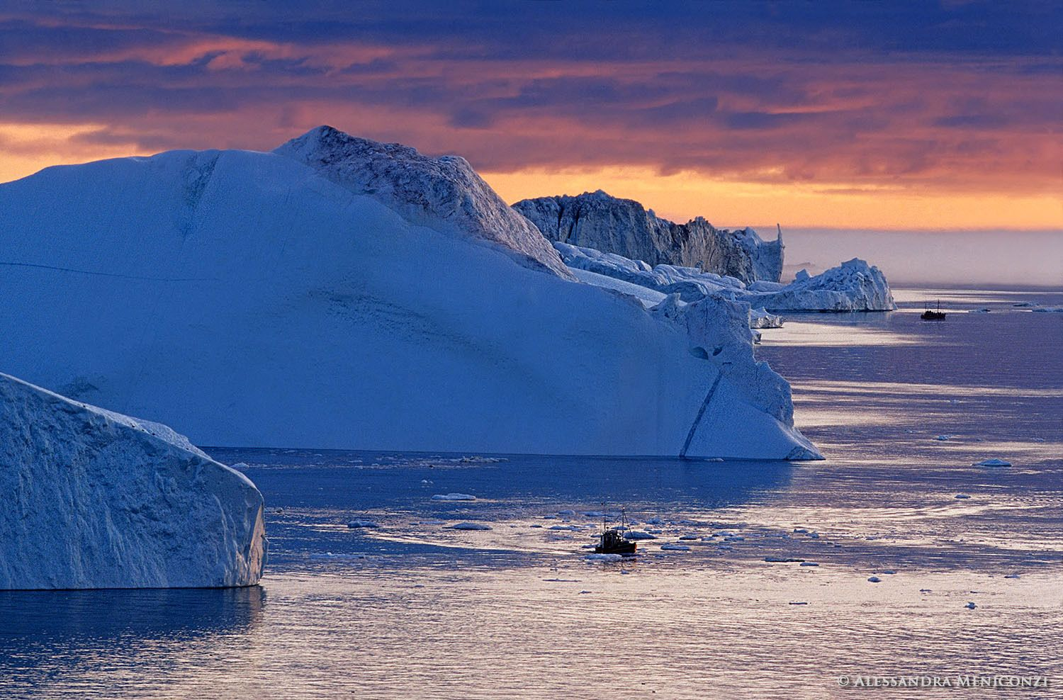 Fishing boats and massive icebergs shed by the Jakobshavn Isbrae glacier in Ilulissat Icefjord at sunset, West Greenland.