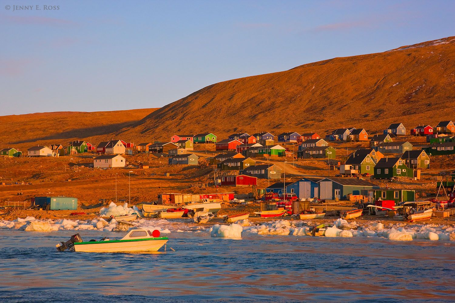 Small boats and colorful houses glow in the early morning light along the shoreline of Qaanaaq, at the edge of Murchison Sound in Baffin Bay, Northwest Greenland.
