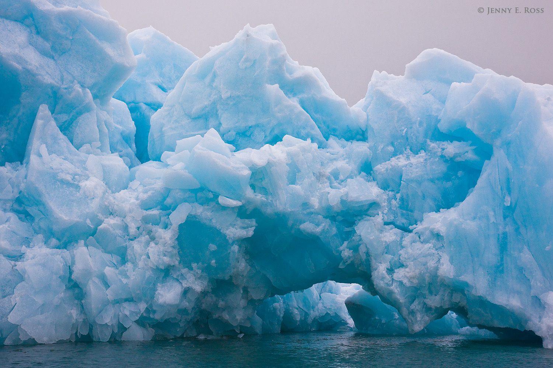 A large iceberg with a natural arch, calved from the Samarinbreen glacier in Samarinvagen on Spitsbergen, Svalbard Archipelago, Norway.