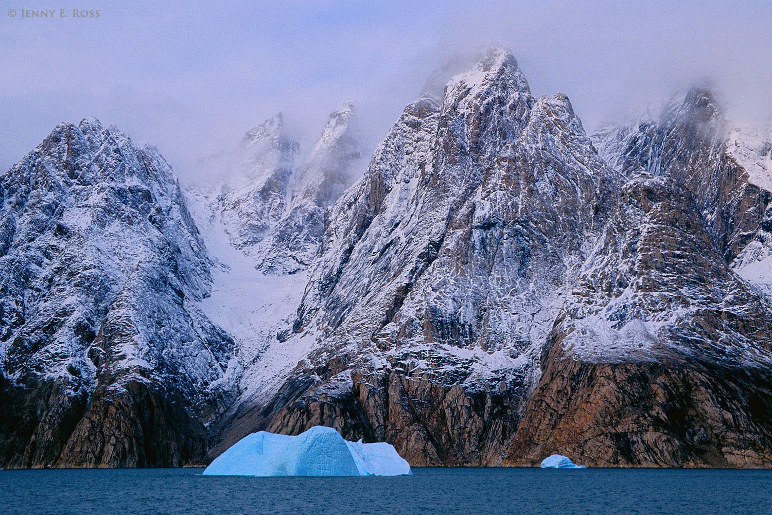 Fog-shrouded mountain spires dusted with snow soar above melting icebergs in Ofjord within Scoresby Sund, East Greenland.