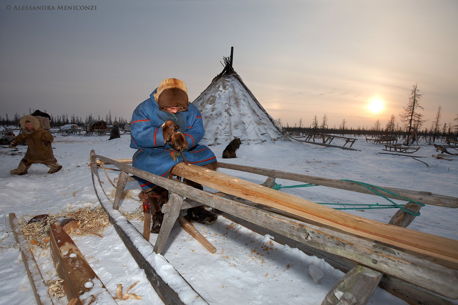 A Nenet man builds a new wooden sledge for use in reindeer herding, outside his family's chum at their winter camp.