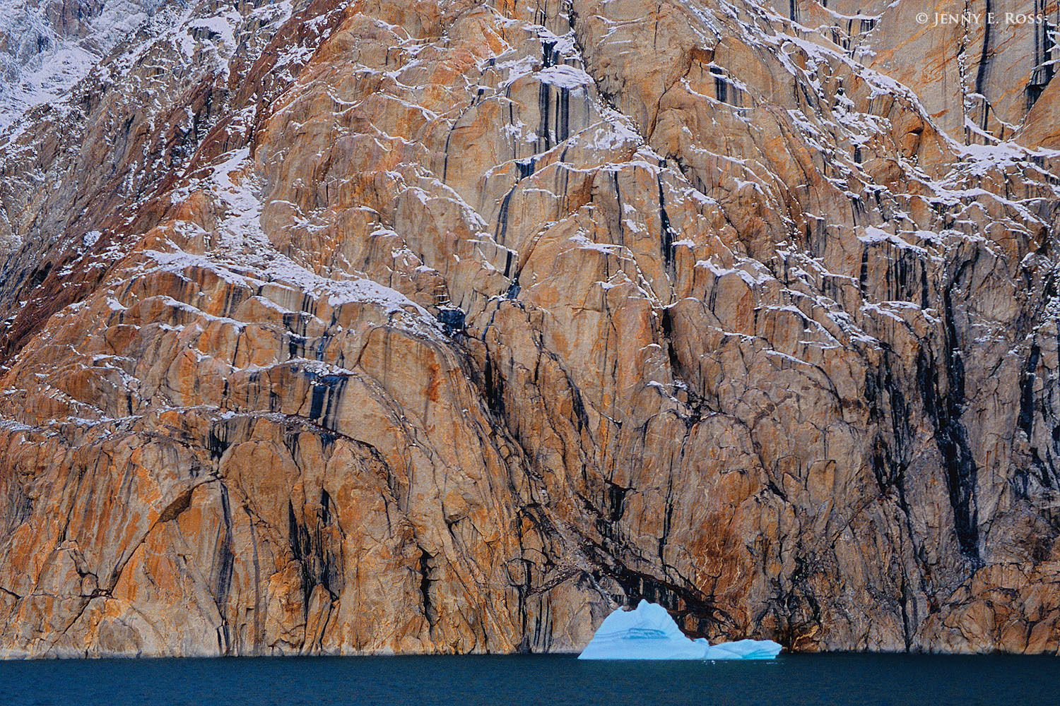 Iceberg, and cliffs adorned with desert varnish and a dusting of snow, in Ofjord within Scoresby Sund, East Greenland.
