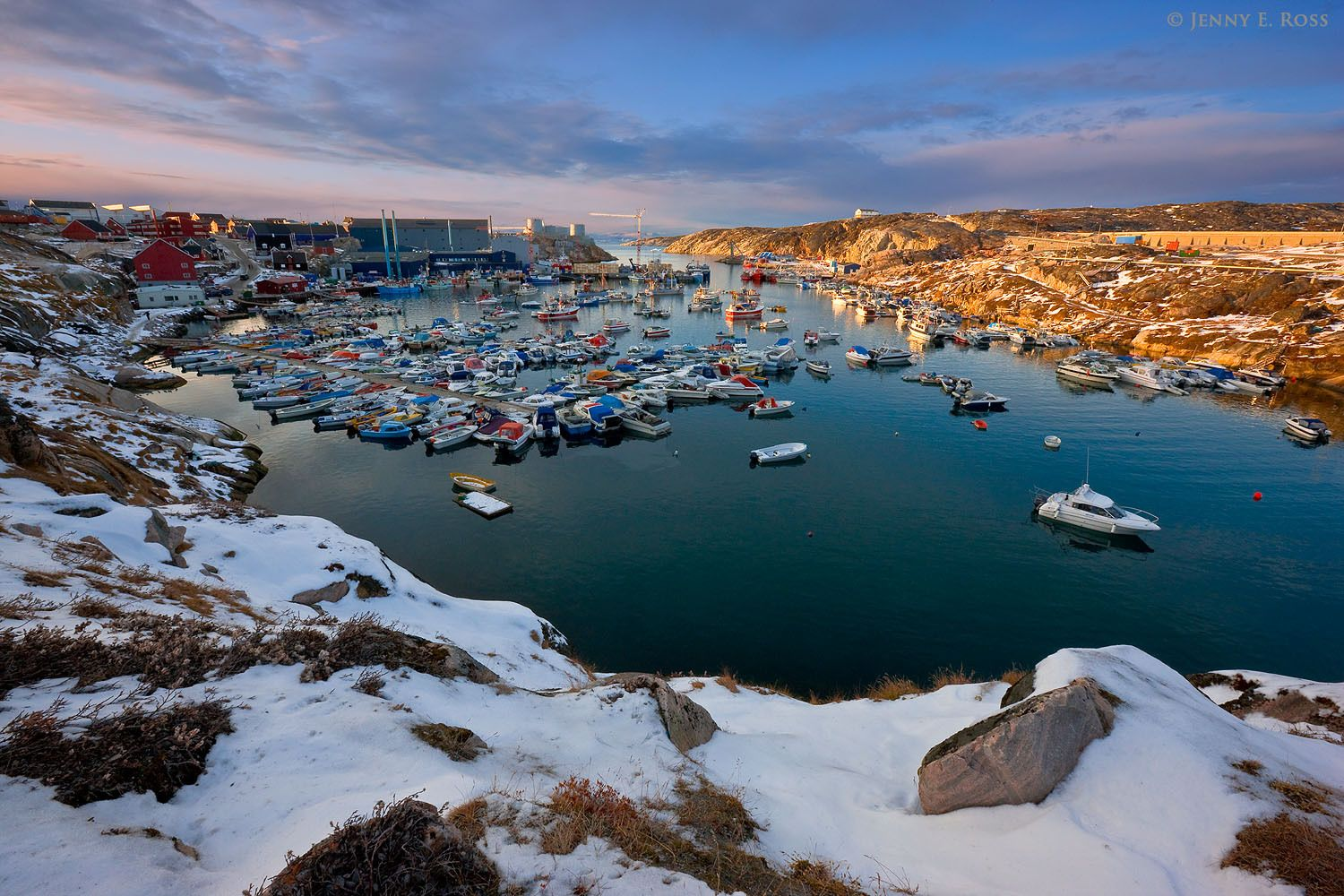 The Ilulissat harbor, filled with fishing boats, in a small fjord connected to Disko Bay in West Greenland.