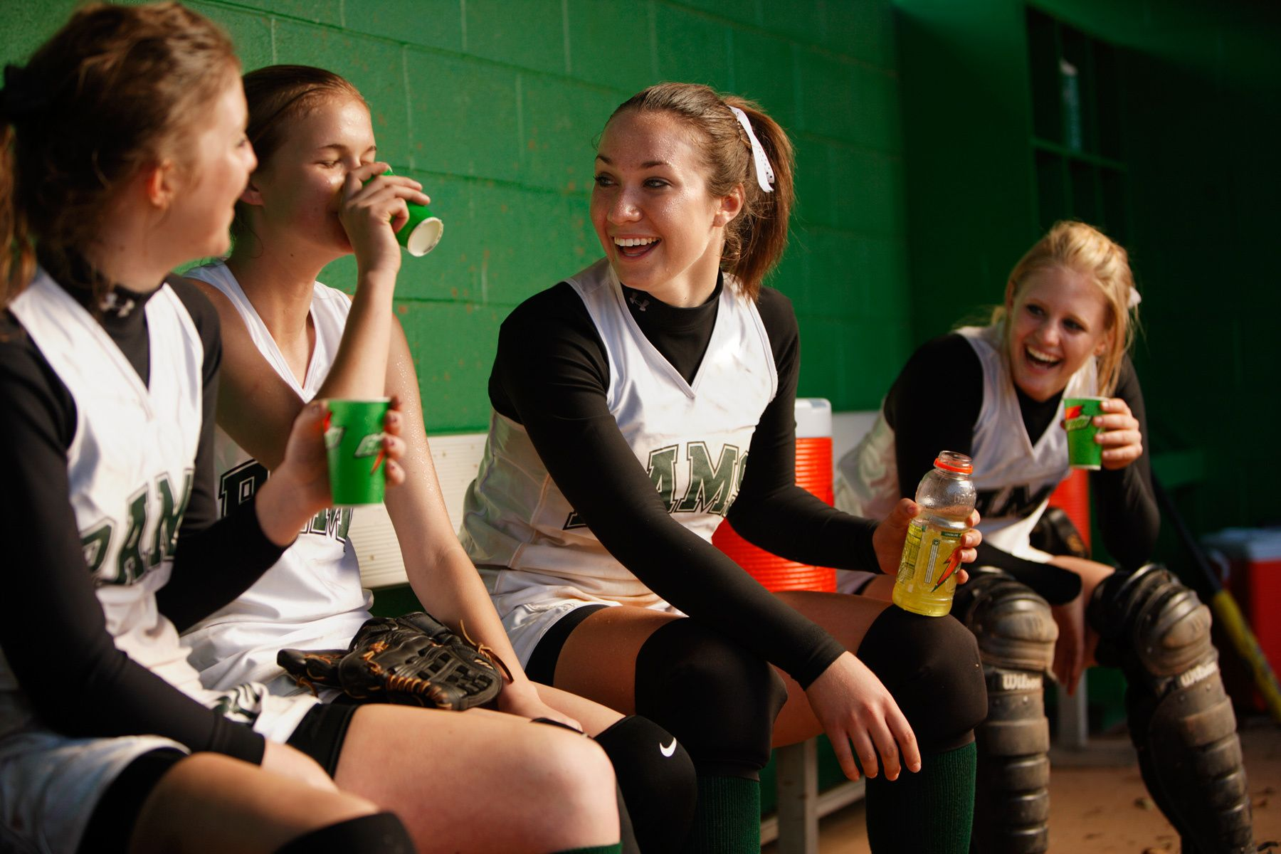 Girls Softball dugout drinking gatorade