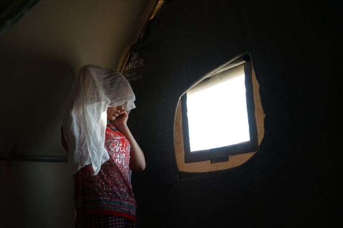 Sarah (her name changed to protect her identity) speaks on the phone inside the tent where she is living with her family in a refugee camp in northern Iraq.