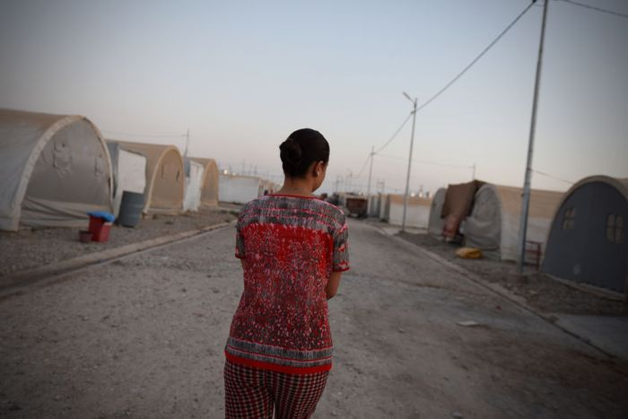 Sarah walks between tents in a refugee camp in northern Iraq where she is living with her parents.
