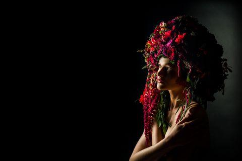 Fashion model wearing a red & crimson floral headdress.  In studio Photo Shoot.