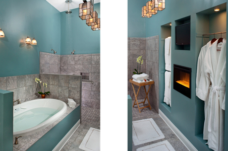 Interior Photograph of a bathroom tub with a shower and fireplace.png
