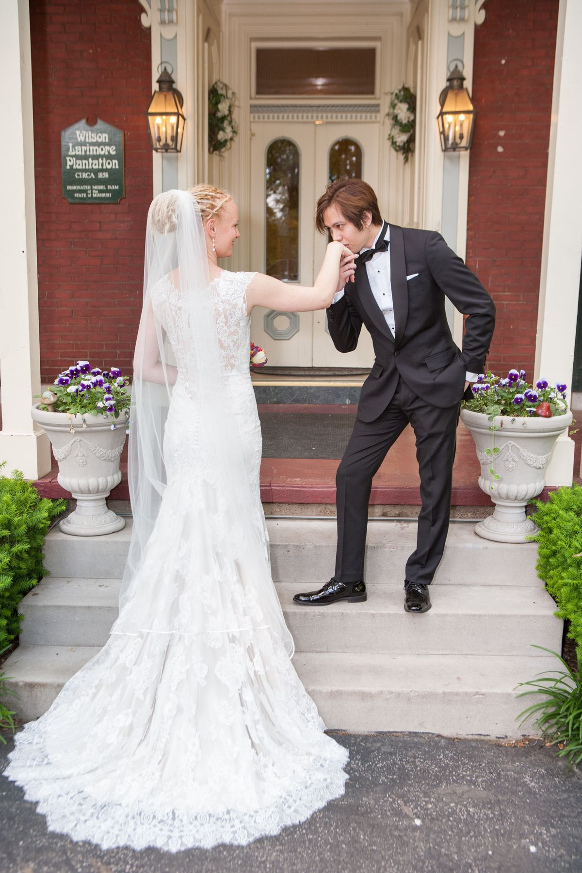 Groom kisses the Bride's hand in a romantic photo