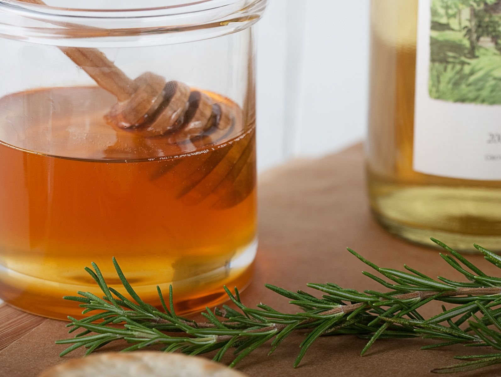 jar of rosemary infused honey with honey dripper