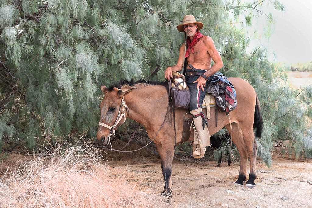 """I GOTTA GET BACK TO NATURE. CIVILIZATION HAS GOTTEN US NOWHERE"" 'Cuervo' and his mule 'Rock 'an' Roll,' Suburbanite Slabbers. Selected for publication in Blurb book and online display in PhotoPlace Gallery juried competition 'Stories and Secrets'"