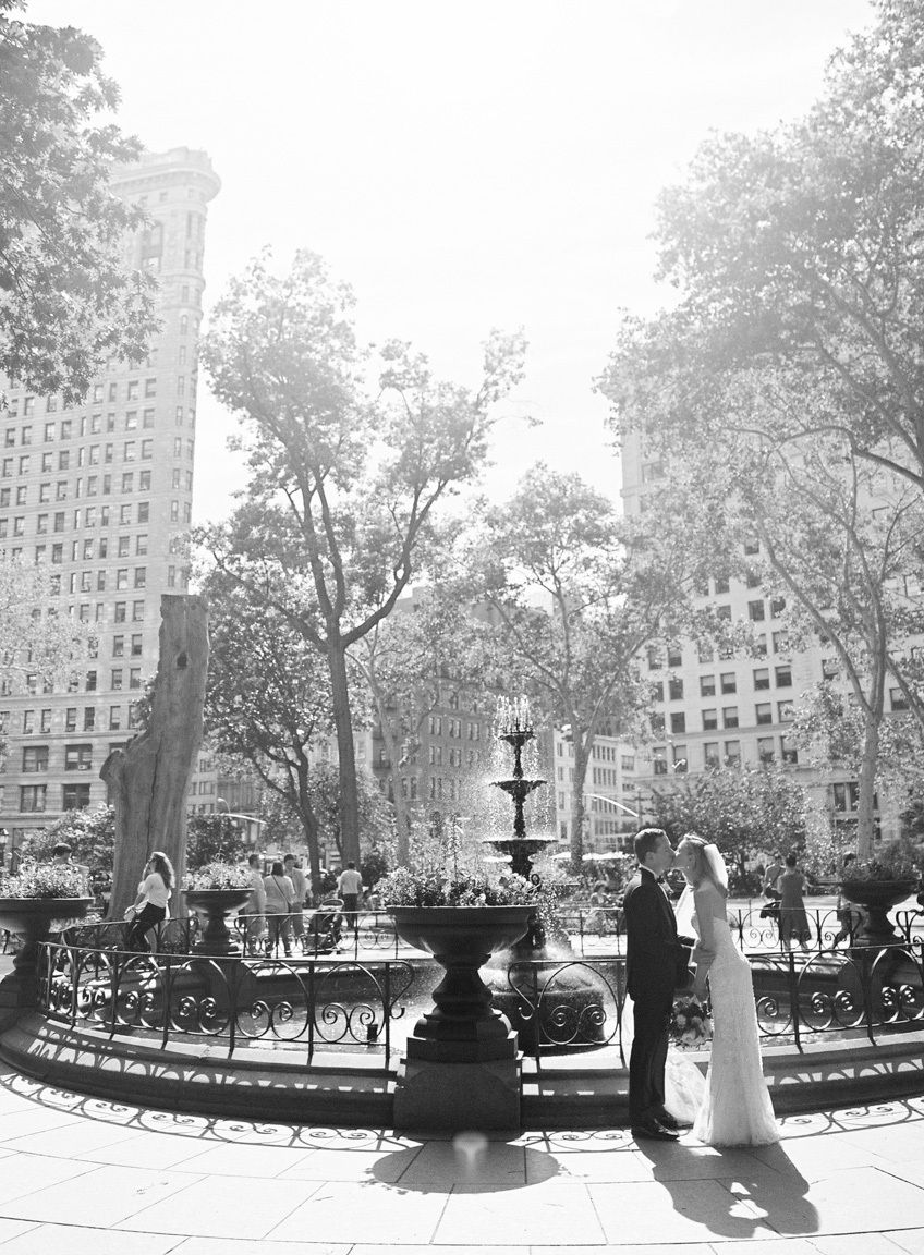 Wedding couple kiss by fountain in Madison Park, NYC