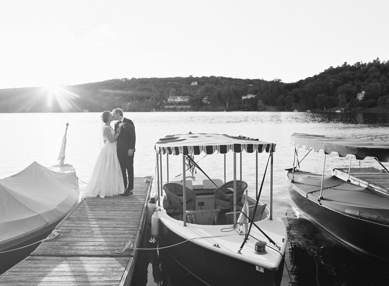 Wedding couple by a lake kissing