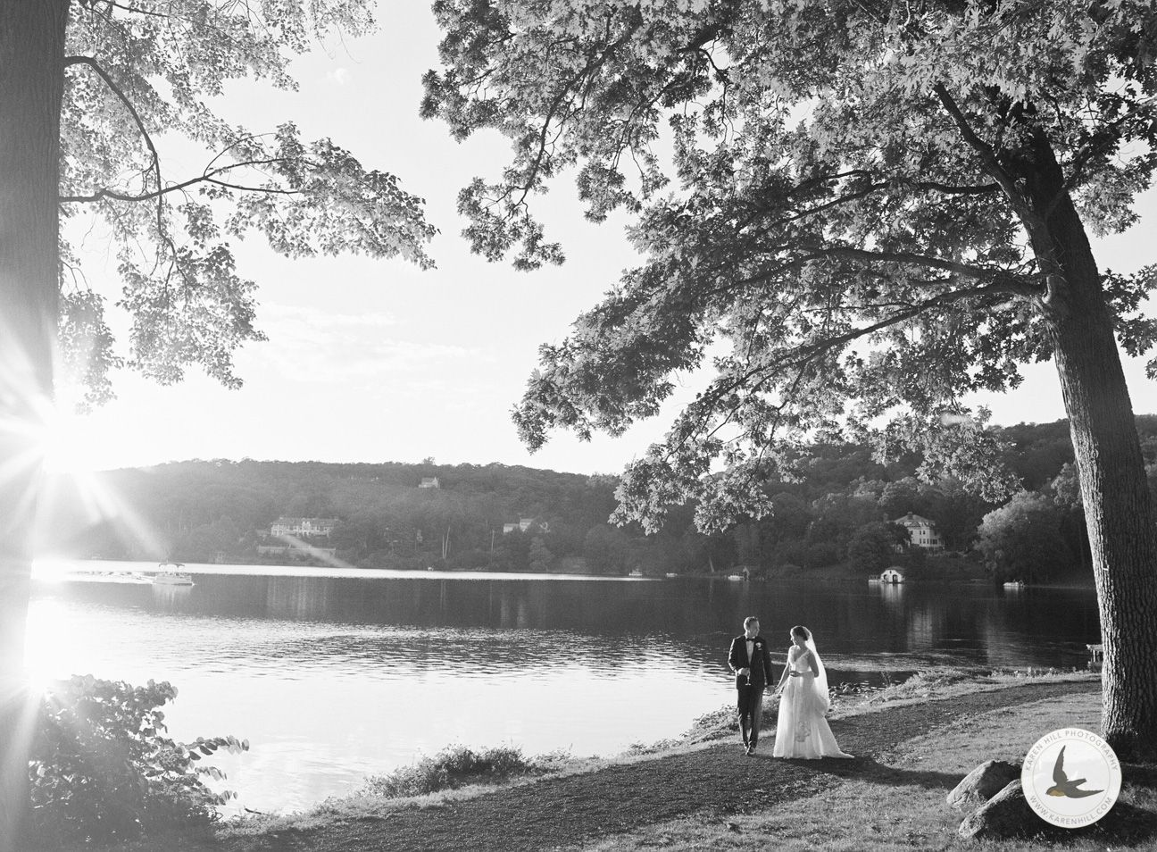Bride and groom walking by lake, by New York Wedding Photographer Karen Hill