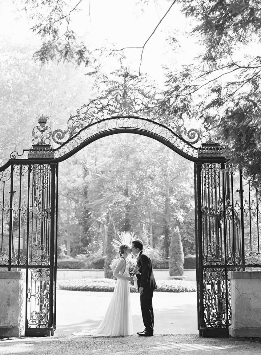 Wedding couple kissing in front of a gate