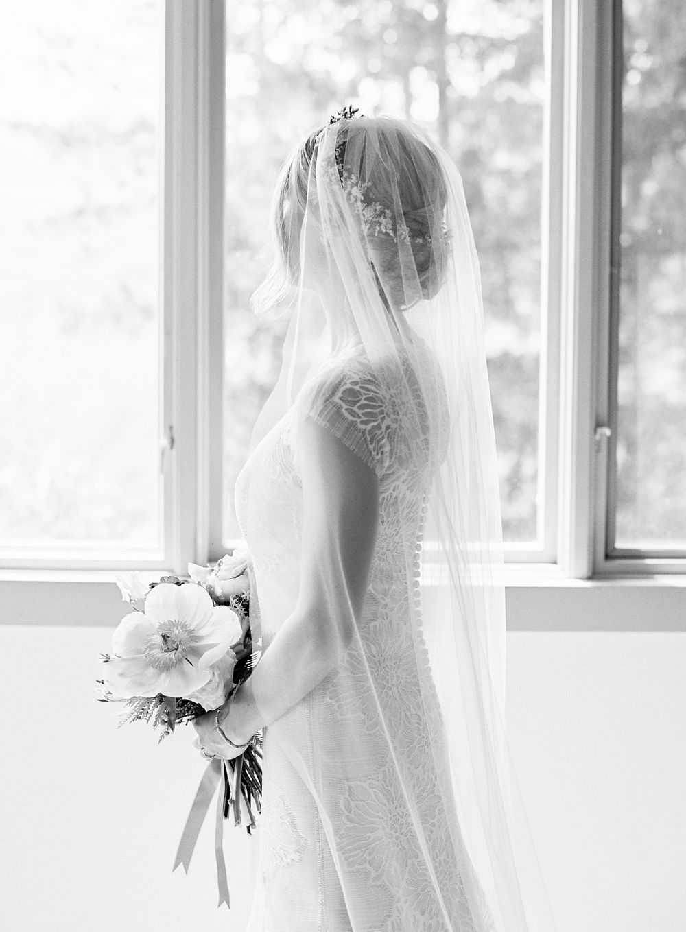 Bride posing in window light holding a bouquet