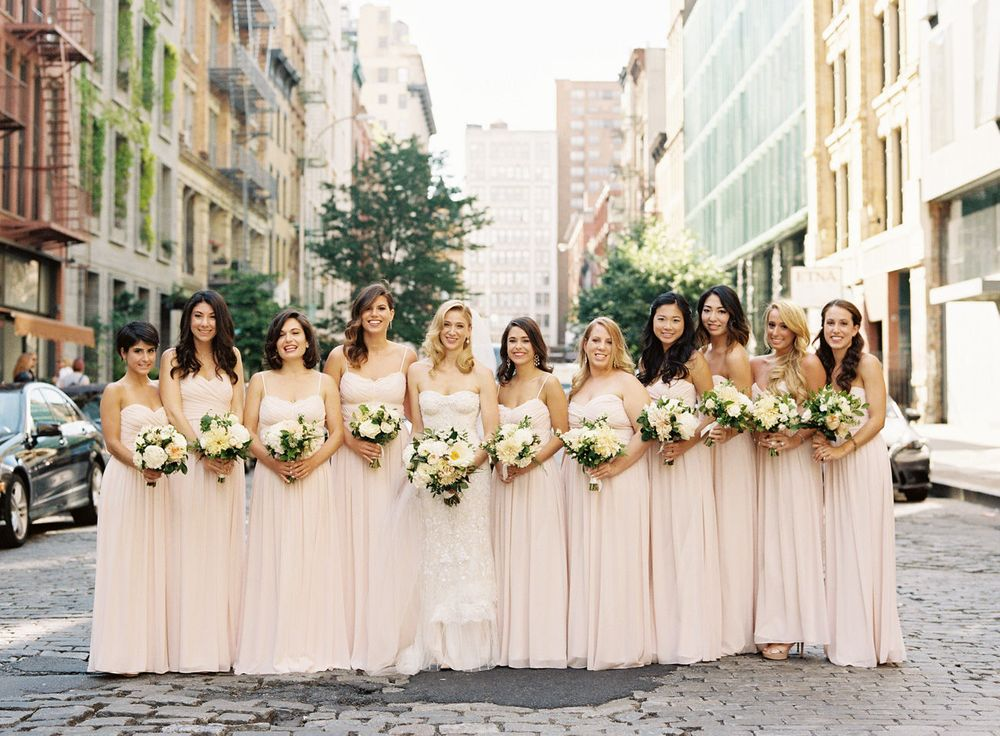 Bride and bridesmaids on a couple stone street