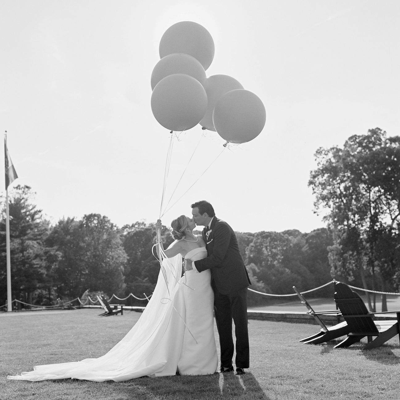Wedding couple kissing holding balloons