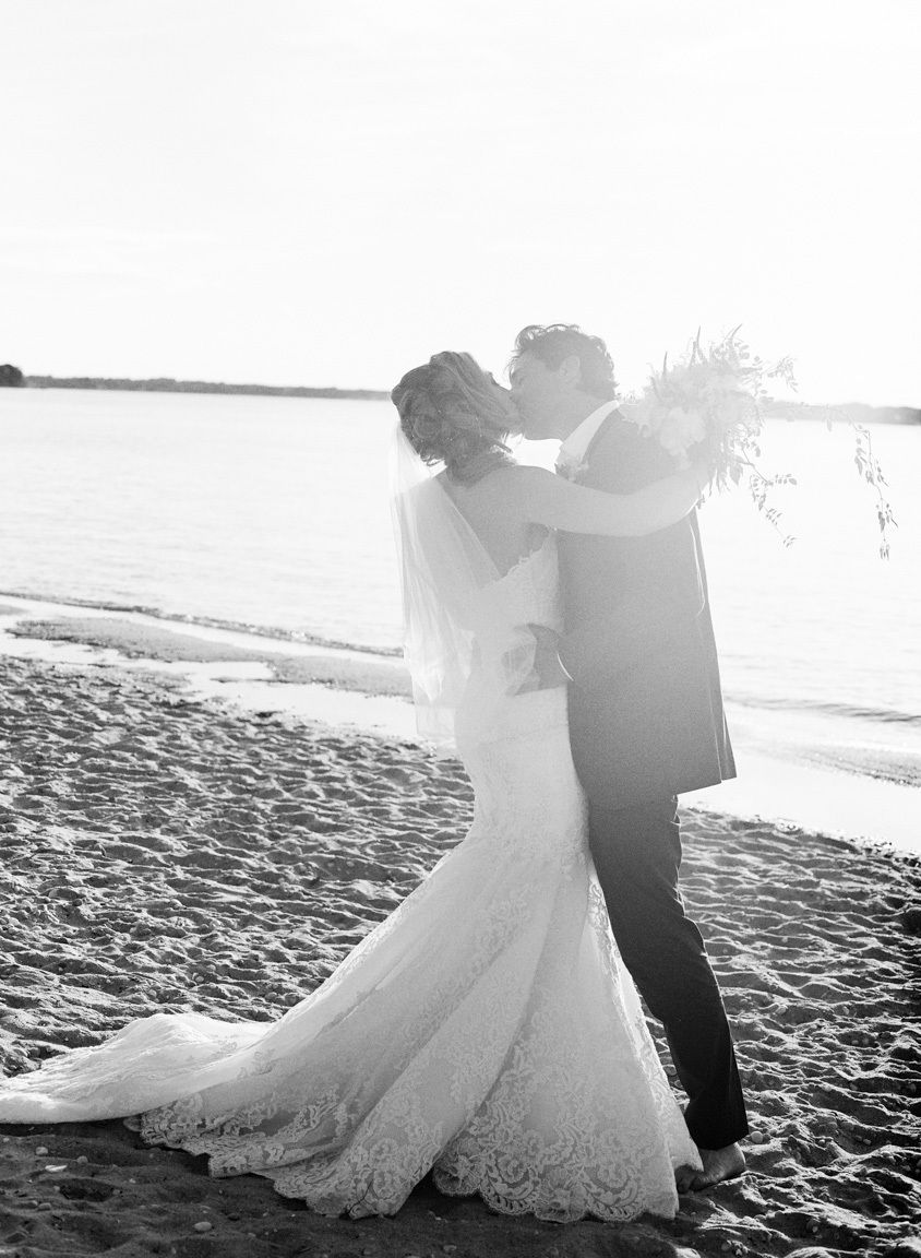 Wedding couple kissing by the shore