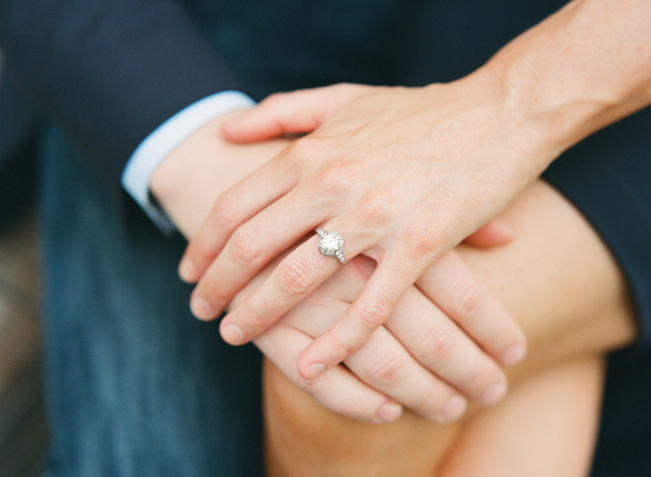Detail of engaged couples hands with a diamond ring