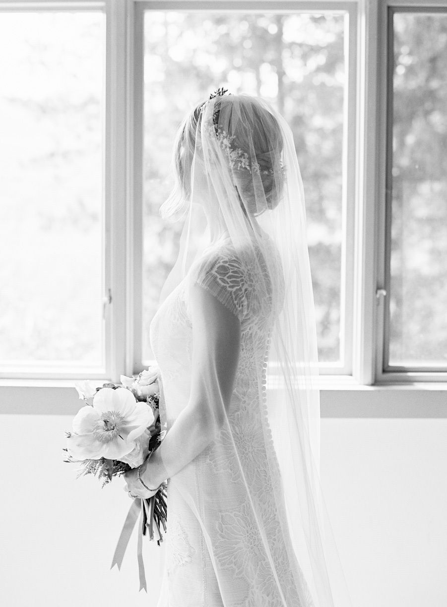 bride posing with bouquet  by a window