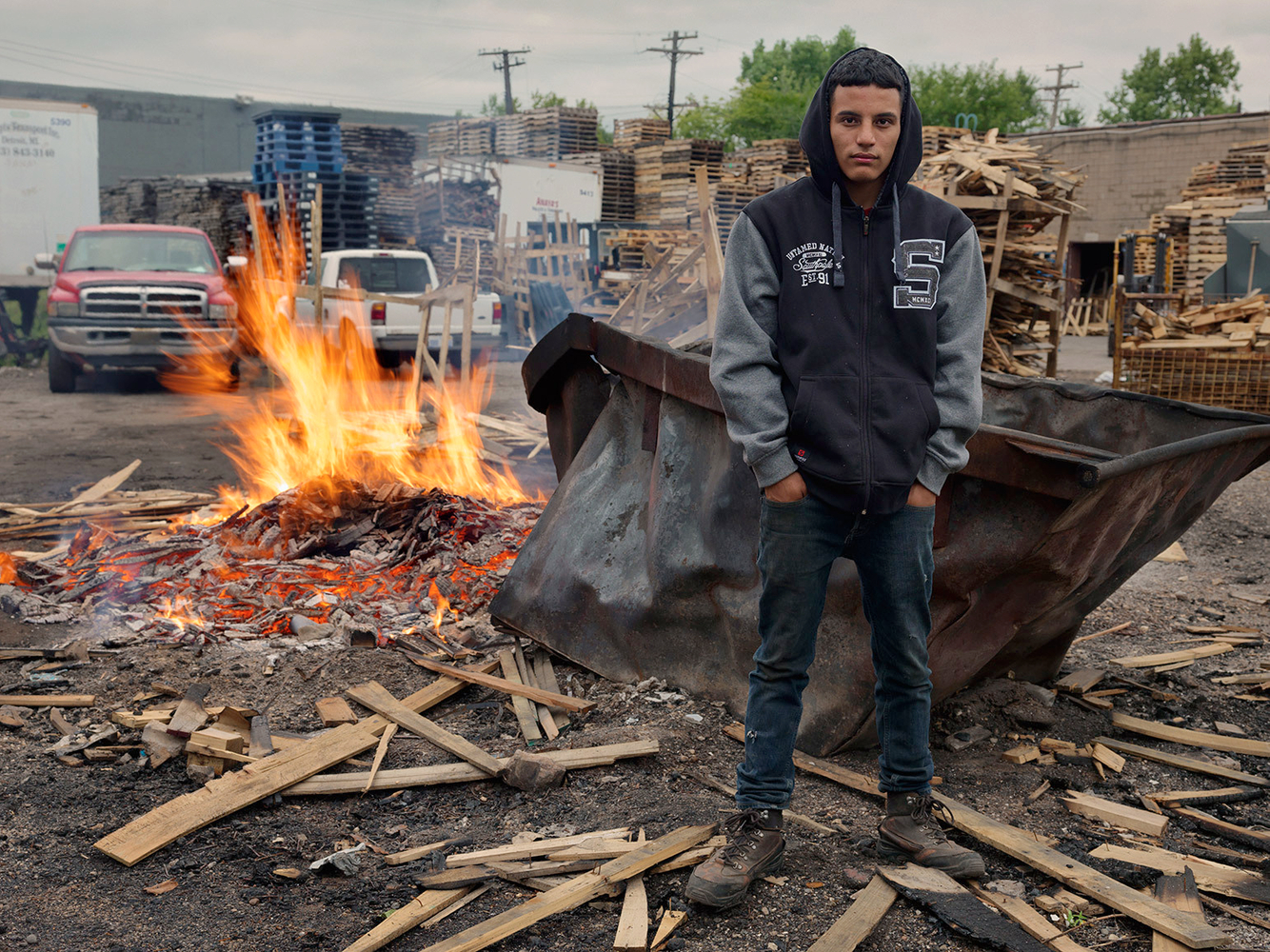 Jonathan Keeping Warm in the Pallet Yard Where He Works, Delray, Detroit 2014