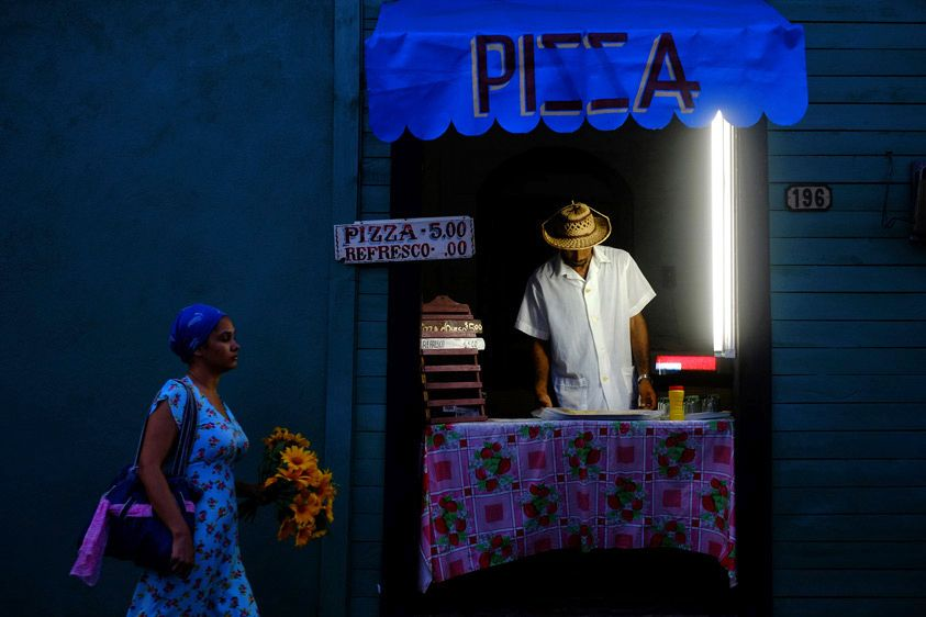 A man prepares to sell pizza from the door way of his home in Baracoa. The Cuban government has eased restrictions and has allowed people to run small businesses from their homes. Baracoa, Cuba.