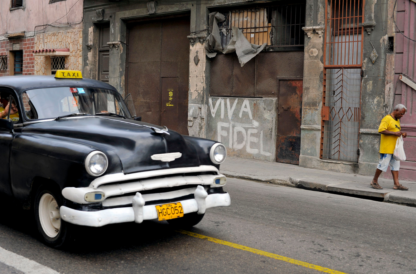A vintage taxi drives by pro-Fidel grafitti in Old Havana, Cuba.