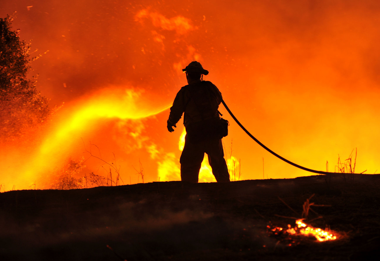 A lone firefighter sprays water on flames