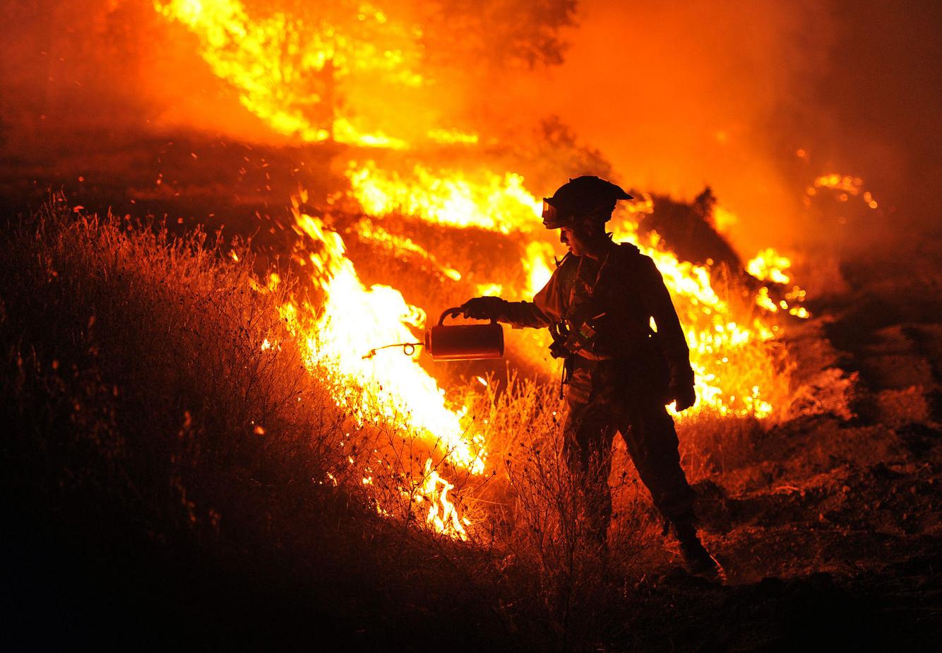 A firefighter lights a backburn