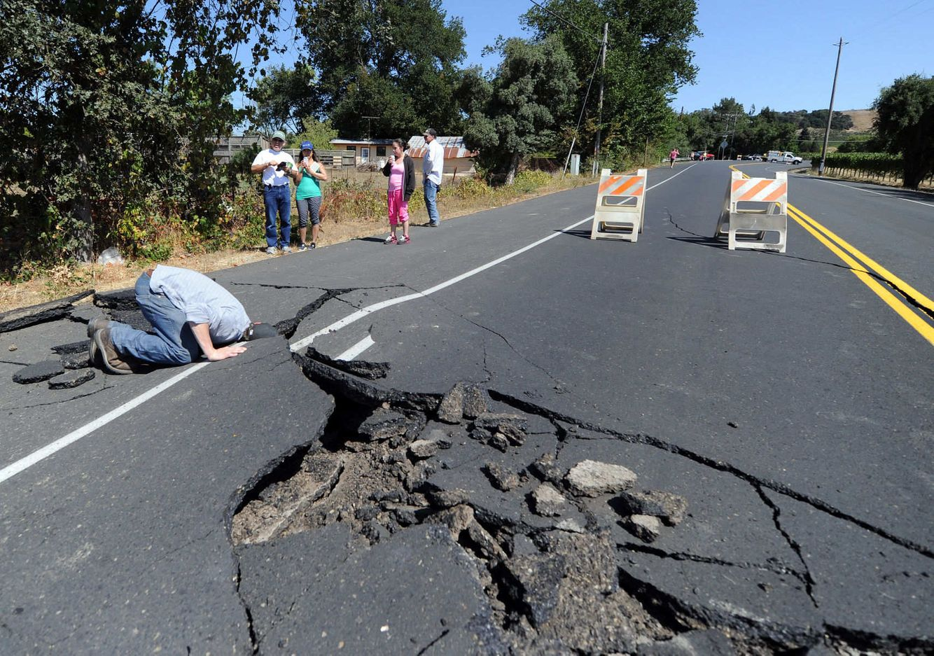 EARTHQUAKE: Nicholas George looks under a buckled highway
