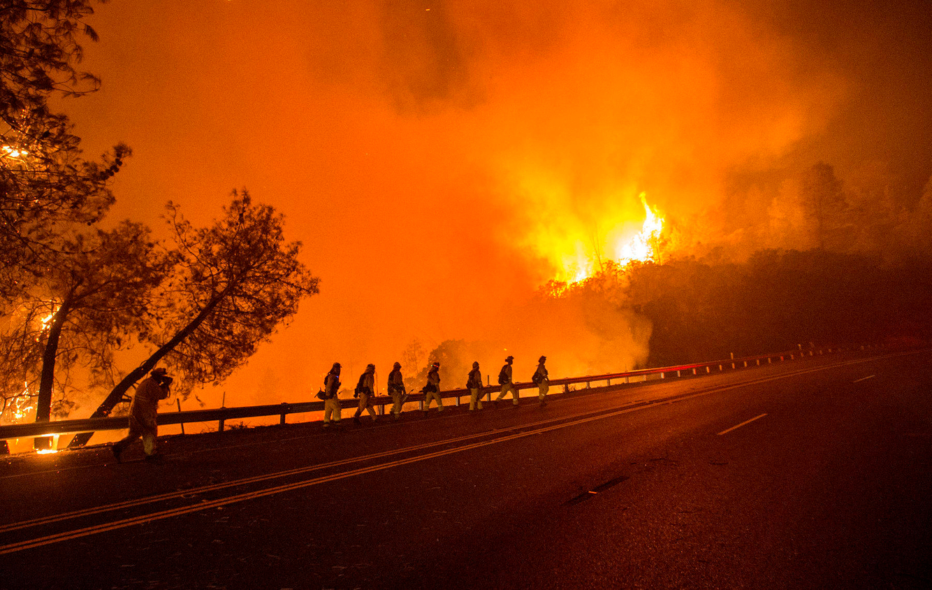 A crew of firefighters walk towards a burning hillside