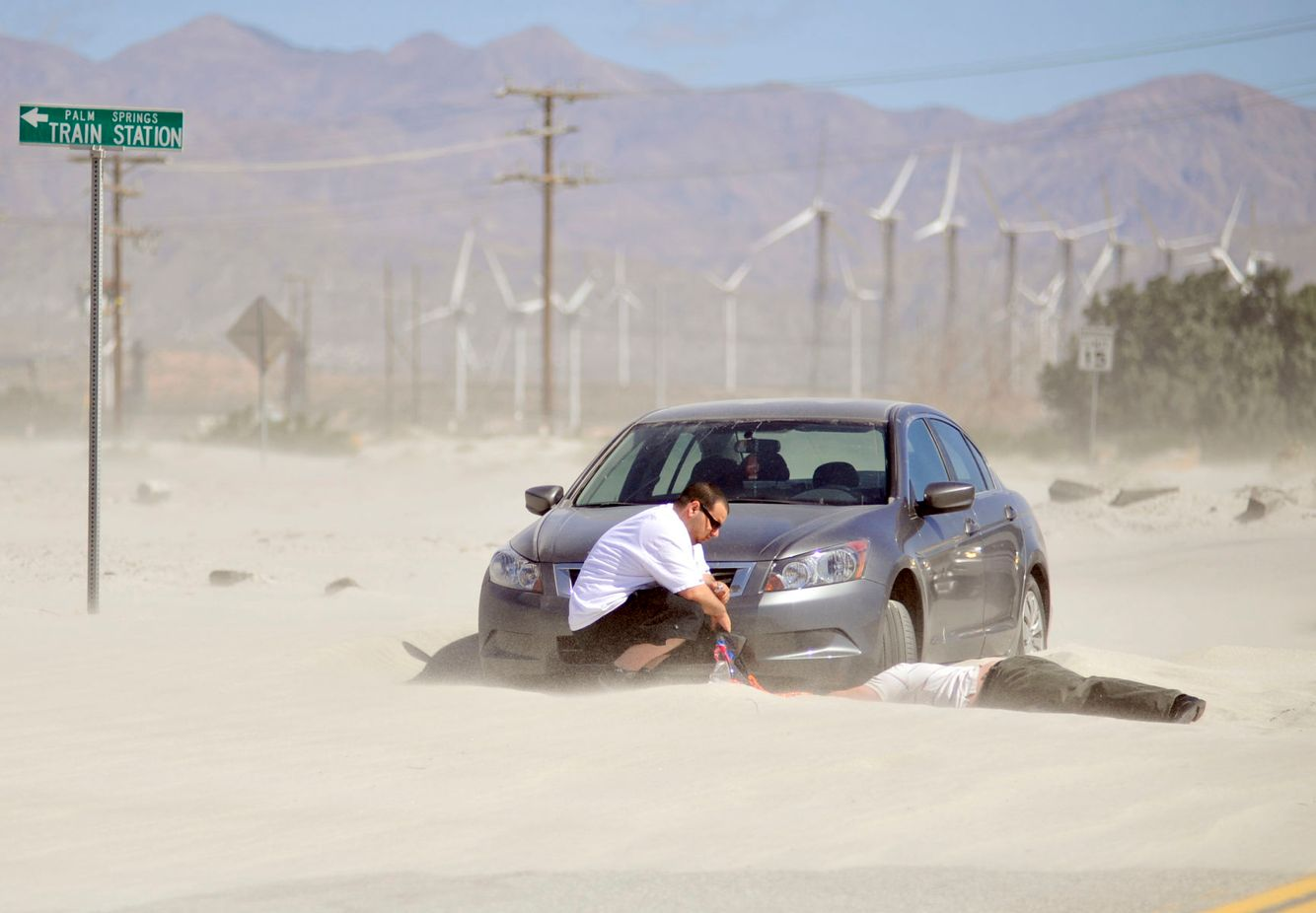 WEATHER: High winds paralyze a car as sand dunes take over a road in Palm Springs.