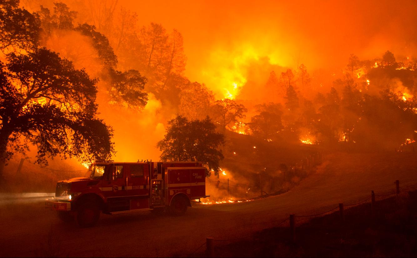 A CalFire truck drives along a burning road