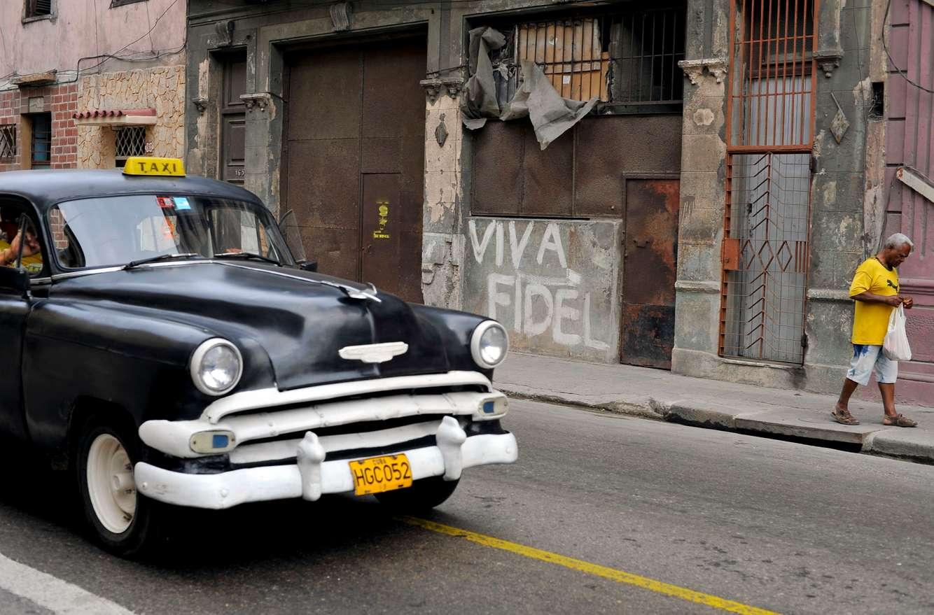 A vintage taxi drives by pro-Fidel grafitti in Old Havana, Cuba.