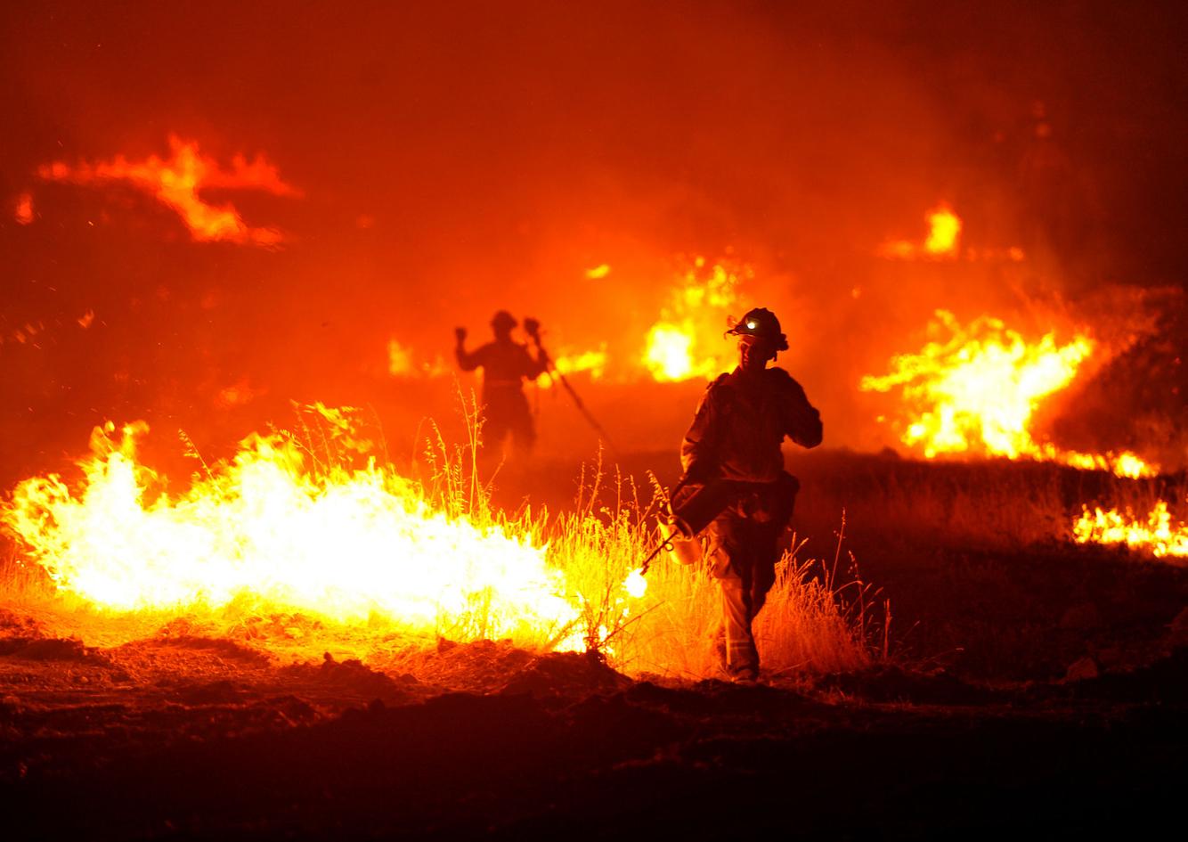 Firefighters light a backfire
