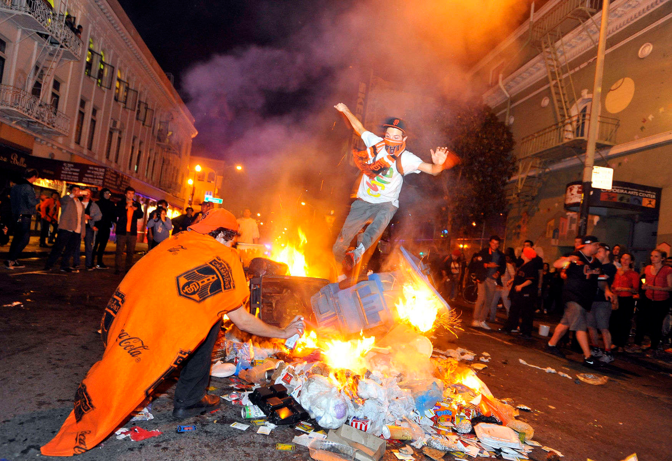 WORLD SERIES REACTIONS: A man jumps over burning trash while vandalism ensues after the Giants beat the Royals in the 2014 World Series in San Francisco.