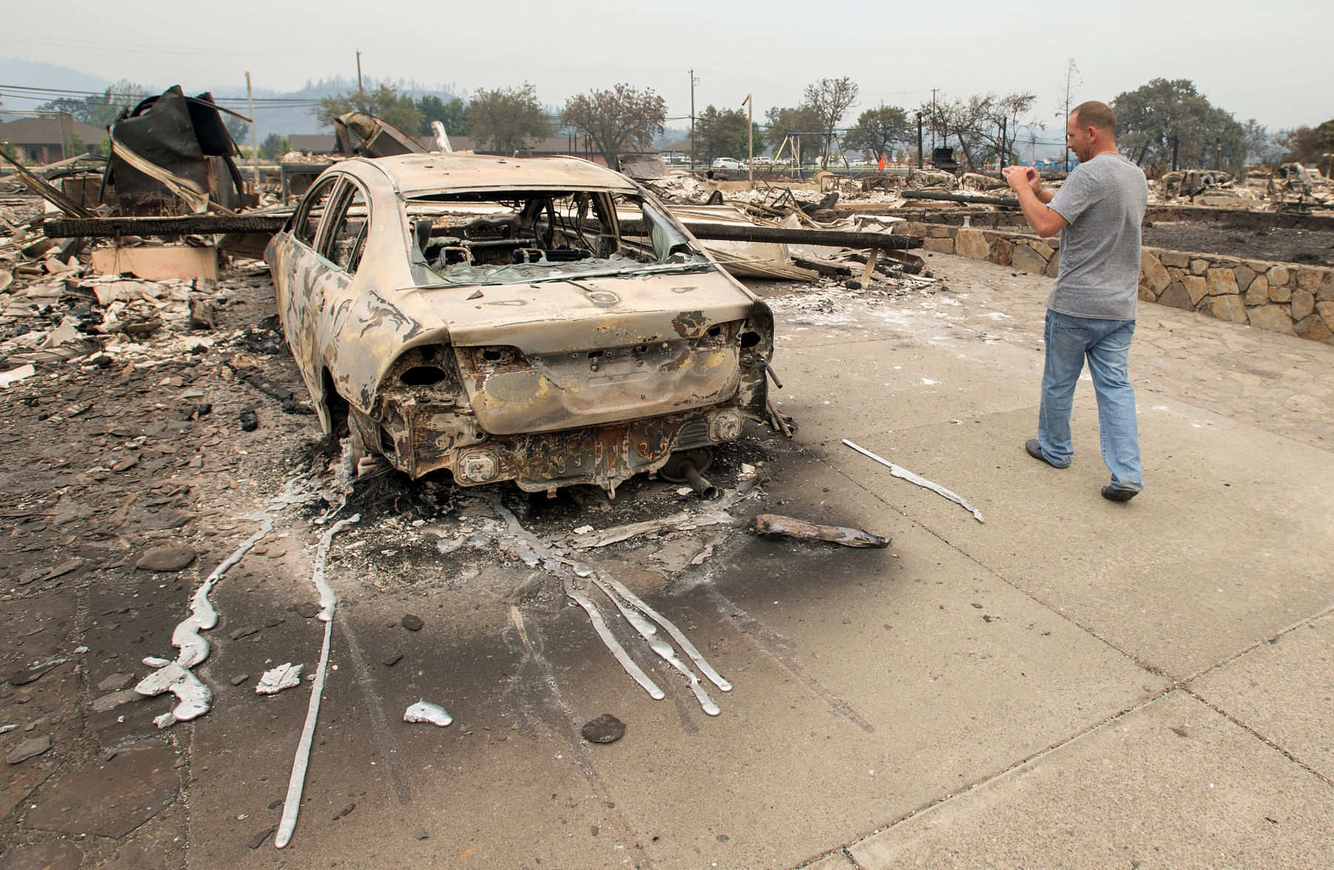 A man takes a photo of his daughter's burned out new car in her driveway after a fire tore through the area.
