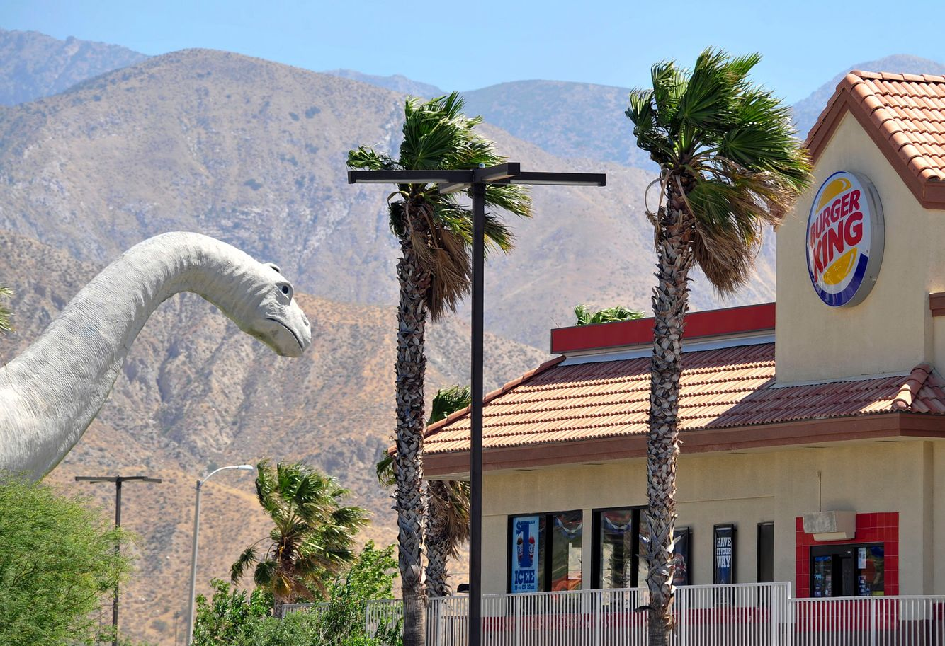 A dinosaur statue is seen near a Burger King in Palm Desert, California.