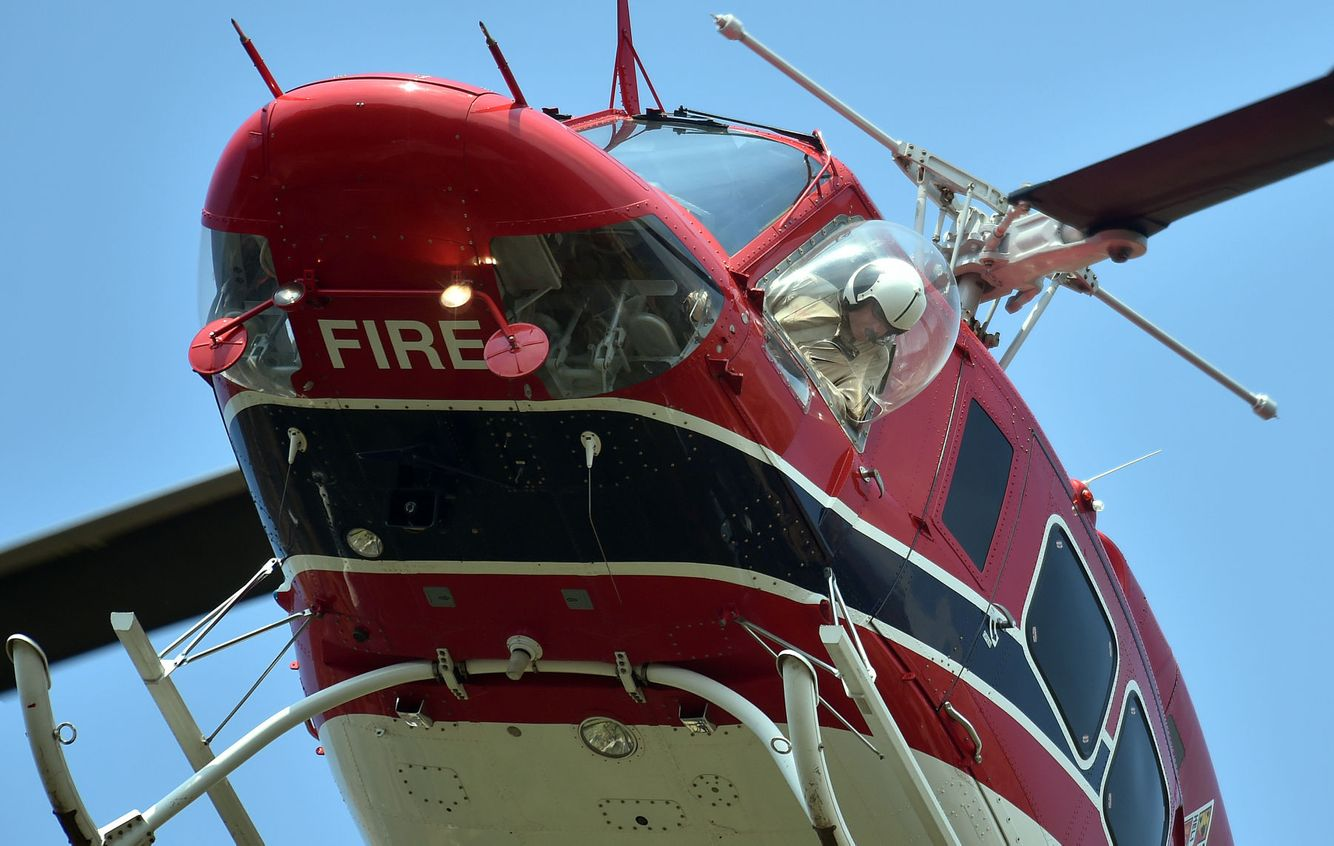 An air support chopper pilot collects water to help fight a fire.