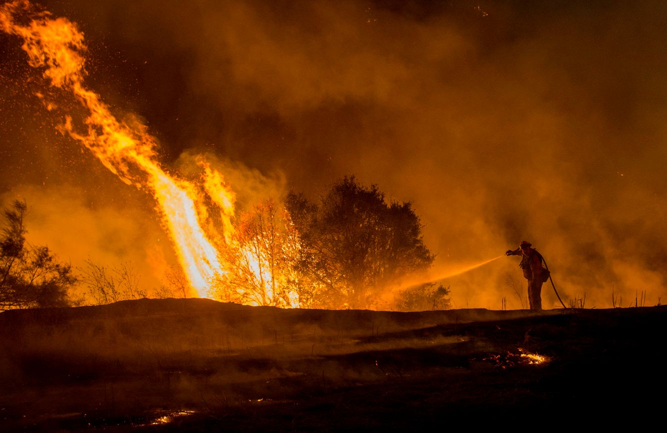 A lone firefighter douses impending flames