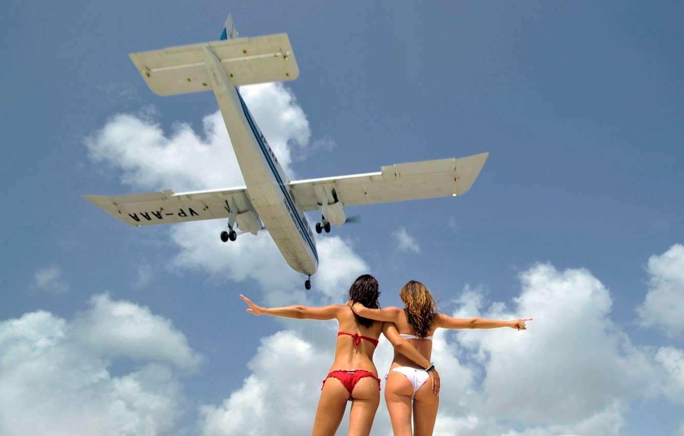 Bikiini-clad sunbathers embrace on a beach as a low-flying aircraft lands at Princess Juliana International Airport in St. Maarten.