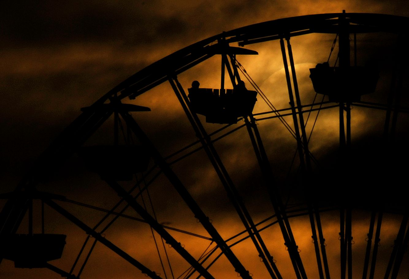 The sun sets behind clouds as people enjoy a Ferris Wheel ride at the Santa Monica Pier
